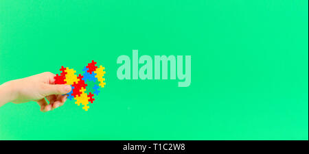 Child hand holding colorful heart on green background. World autism awareness day concept - Stock Photo