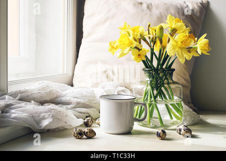 Cozy Easter, spring still life scene. Mug of coffee, wooden plate, quail eggs and vase of flowers on windowsill. Floral composition with yellow daffod - Stock Photo