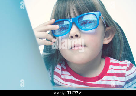 Technology genius concept. Little girl programming on a laptop - Stock Photo