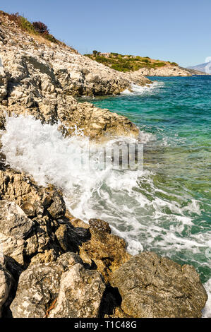 Phenomenal and scenic sea waves crashing against the rocky coast. Another sunny day during summer vacation in Greece, with view from seashore on blue, - Stock Photo