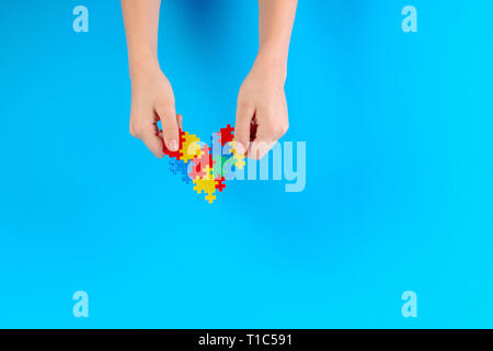 Child hand holding colorful heart on blue background. World autism awareness day concept - Stock Photo
