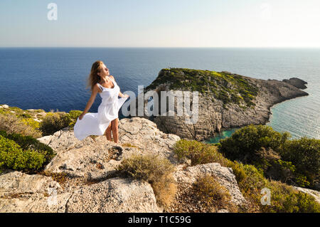 Woman in long white, waving dress is standing on cliff edge with view from above on sea and island. Sunny seascape with female tourist feeling free du - Stock Photo