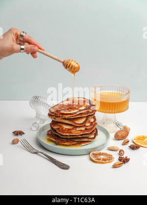 Woman pours honey on pancakes. The concept of a delicious breakfast. - Stock Photo