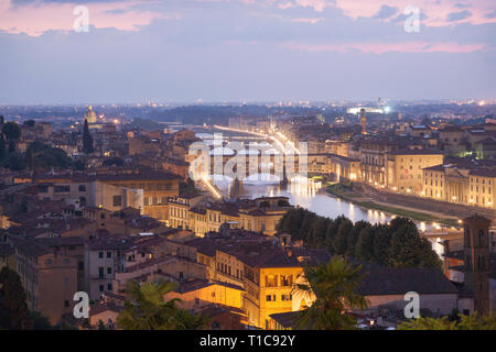 Elevated view over Florence towards the Ponte Vecchio bridge across the river Arno at dusk. - Stock Photo