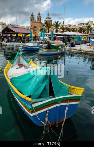 Traditional colourful Maltese fishing boats known as luzzu, Marsaxlokk, Malta - Stock Photo