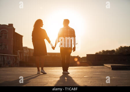 Couple holding hands and walking through the city street - Stock Photo