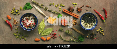 Different spices in spoons, bowls on a brown rustic background. Condiments for cooking. Top view - Stock Photo