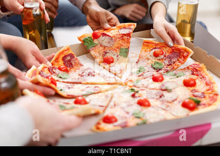 Friends eating delicious pizza at home party - Stock Photo