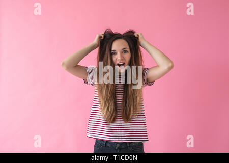 Surprised girl with disheveled hair expresses emotions on a pink background. - Stock Photo