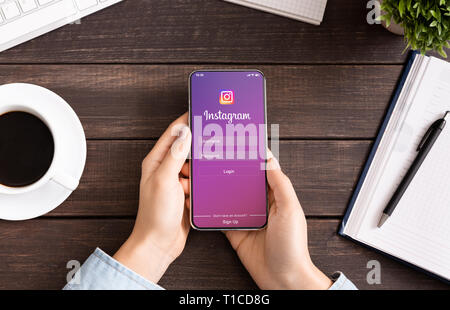 Woman holding iPhone with Instagram application on screen. - Stock Photo