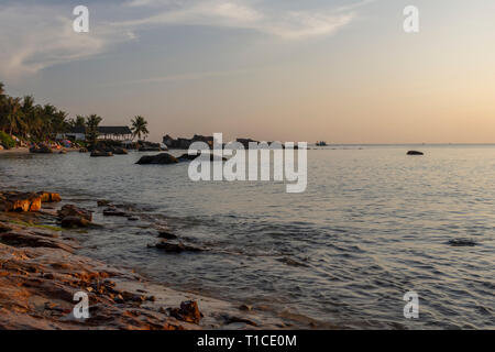 Rocky shore and a calm sea in golden hour with palm trees and a blue sky with some clouds in background, picture from Long Beach on Phu Quoc Island, V - Stock Photo