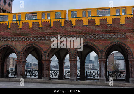 Yellow subway cars driving on the Oberbaunum bridge , it links Friedrichshain and Kreuzberg, Berlin, Germany - Stock Photo