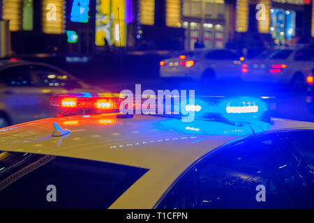 Red and blue flashing lights on police car in the night. - Stock Photo