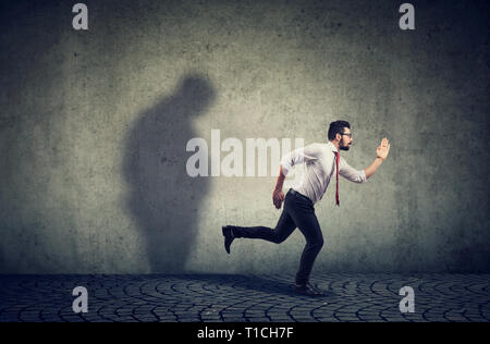 Man running away from his sad gloomy fat shadow on the wall. Mental health and body weight control concept - Stock Photo