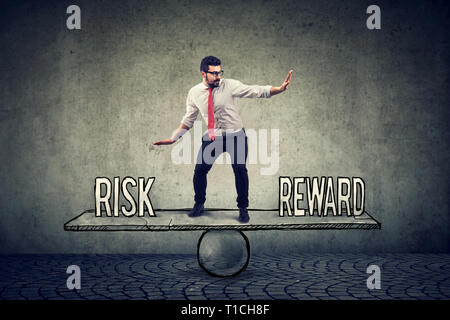 Skillful young business man balancing between reward and risk in challenging corporate environment - Stock Photo