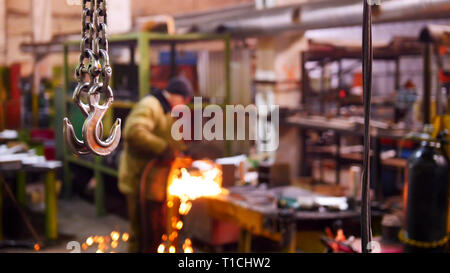 Construction plant. A big industrial lifting chain with a hook on the end. A man welding on the background - Stock Photo