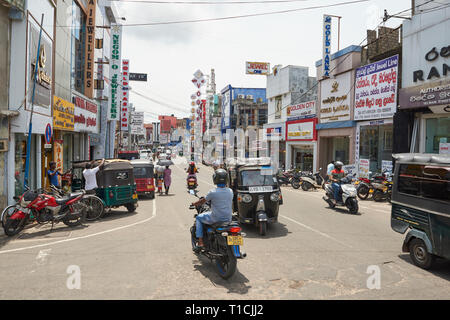 Busy commercial road in Negombo, Sri Lanka, on a sunny day, with heavy traffic of bicycles, cars, motorbikes and tuk-tuks. - Stock Photo