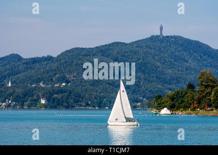 WORTHERSEE, AUSTRIA - AUGUST 08, 2018:  Worthersee view at turquoise water of lake in summer mountains in distance. Tourists enjoying summer vacations - Stock Photo