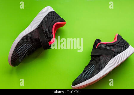 Fashion running shoes ,kids Sport shoes.children sports sneakers of black color, casual shoes isolated on green.Sport spring summer girl shoes. - Stock Photo