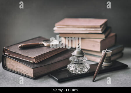 Vintage set with antic books, old stationery, wooden pen, inkwell, magnifier close-up on desk, . Concept of reading and education, memory and nostalgy - Stock Photo