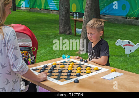 Dnipro, Ukraine - June 27, 2018: Young sportsman play checkers on day of opening of inclusive city park - Stock Photo
