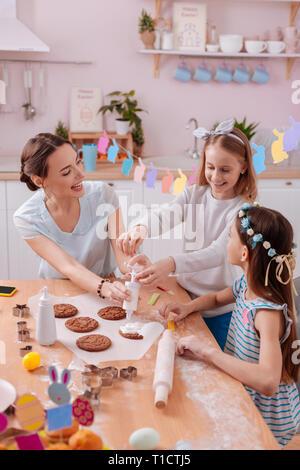 Joyful females decorating cookies together with pleasure - Stock Photo