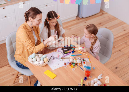 Low angle picture of happy family that painting eggs - Stock Photo