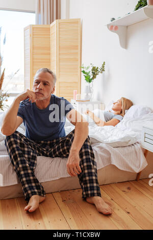 Businessman sitting on bed feeling overloaded with thoughts