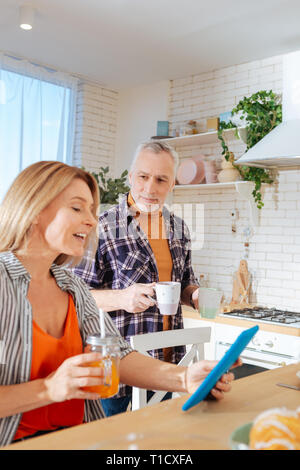 Couple enjoying morning together drinking tea and reading news - Stock Photo