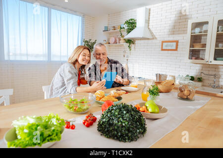 Businessmen reading news on tablet enjoying healthy breakfast - Stock Photo