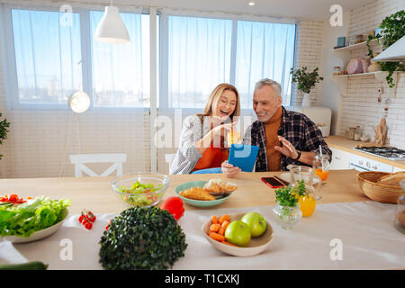 Beaming couple having much fun while enjoying breakfast - Stock Photo