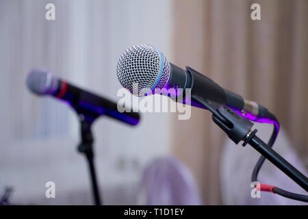Microphone on the Stand is Standing on the Stage, Close-Up Microphone on the Background of the Auditorium, Spotlight, Backlight People Gather in the H - Stock Photo