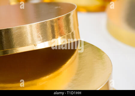 Gold and white coasters for cakes, rings for decorating cakes, baking tools, selektive focus - Stock Photo