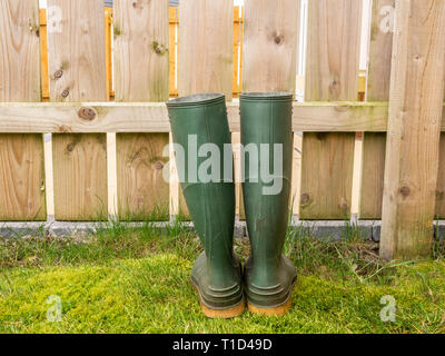 Wellington boots by a fence in a garden - Stock Photo