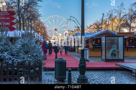 People walking along Christmas market by booths full of gifts and souvenirs. Christmas fair in the Brussels center. - Stock Photo