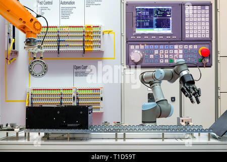 Industrial robotics working via conveyor belt on smart factory, terminal and control panel background, industry 4.0 concept - Stock Photo