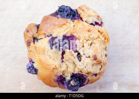 Homemade vegan blueberry muffin presented on a wooden plate - Stock Photo