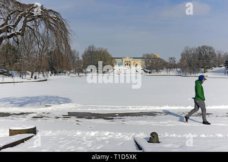 A solitary man walks around the snow-covered pond outside the Cleveland Museum of Art during the winter in Cleveland, Ohio, USA. - Stock Photo