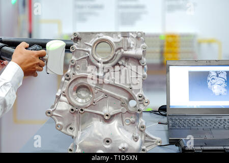 Hands of technician use 3D scan for scan part of automobile on show in the old laptop display on blurred background, industry 4.0 concept - Stock Photo