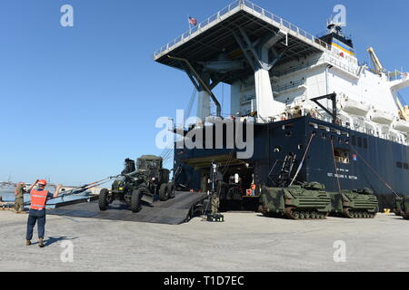 190318-N-MW964-1070 PORT HUENEME, Calif. (Mar. 13, 2019) Seabees from Naval Mobile Construction Battalion 5 and Marines from I Marine Expeditionary Force direct the offload of a road grader from the Military Sealift Command vessel USNS SGT William R. Button (T-AK 3012) during maritime prepositioning force training in support of Pacific Blitz 2019 (PacBlitz19). The inherently dynamic, scalable, and combined-arms capability of MAGTFs joined with mobility and sustainability provided by amphibious ships gives us an asymmetric advantage over adversaries.  PacBlitz19 increases the ability of all par - Stock Photo