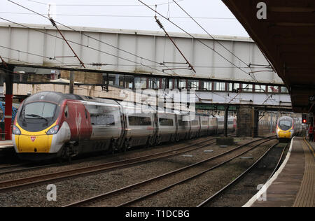 Two Virgin West Coast Pendolino electric trains at Lancaster station on the West Coast Main Line on 21st March 2019, one arriving and one leaving. - Stock Photo
