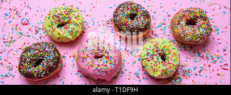 Donuts assorted. Doughnuts with colorful sprinkles and icing on pink background, top view, banner - Stock Photo