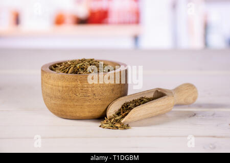 Lot of whole roman caraway seeds with wooden bowl in a white kitchen - Stock Photo