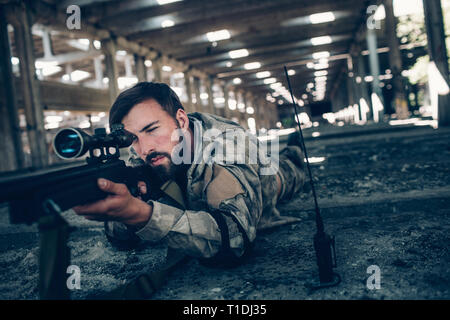 Calm and peaceful young man is lying on the ground and taking aim. He looks very serious. Guy is using rifle for that. Also he is looking through lens - Stock Photo