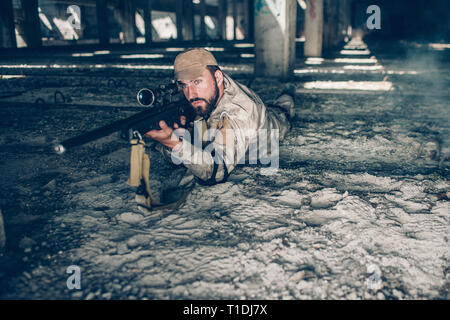 Serious and professional man is lying on the ground and looking through lens. He is taking aim. Guy wears military clothes. He is waiting. - Stock Photo