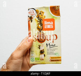 Paris, France - Jul 6, 2018: Man hand holding against white background a pack of Bio Organic Lima Miso prepared ready to eat soup - Stock Photo