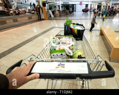 Frankfurt, Germany - Jul 6, 2018: POV man hand pushing supermarket car aisle entering DM drogerie Markt supermarket with pouch containing multiple non-food items - kids having fun outside shopping center - Stock Photo