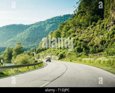 Schiltach, Germany - Jun 10, 2018: German highway with Suzuki SUV SUV car driving fast on the rural highway on a sunny day with Black Forest mountains in background - Stock Photo