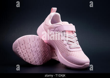 Unbranded pink running shoes on a black background - Stock Photo