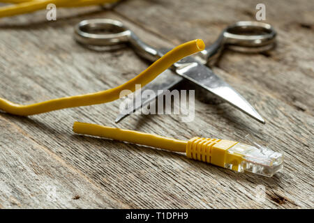 Network cable and scissors on wooden background - Stock Photo